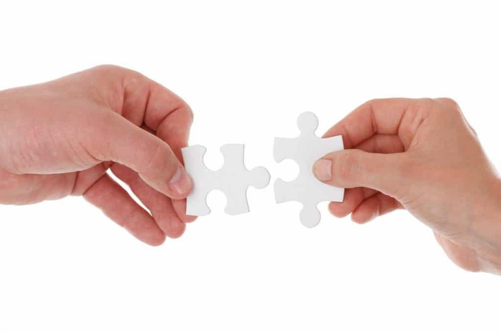 mãos encaixando um quebra-cabeça