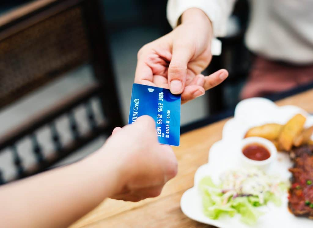 Imagem de uma pessoa entregando um cartão de crédito para outra para pagar sua refeição.