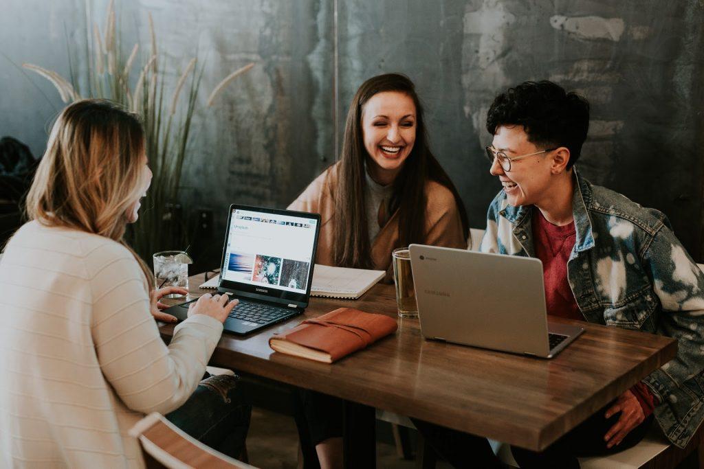 pessoas sentadas em uma mesa de reunião felizes e motivadas com employee experience